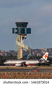 Sydney, Australia - October 7, 2013: Jetstar Airways Airbus A320 twin engine passenger aircraft taxis past the air traffic control tower at Sydney Airport.