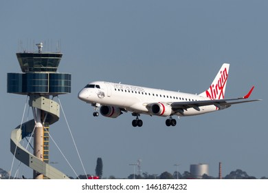 Sydney, Australia - October 7, 2013: Virgin Australia Airlines Embraer E-190 twin engine regional jet airliner landing at Sydney Airport with the air traffic control tower in the background.