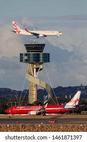 Sydney, Australia - October 8, 2013: Virgin Blue Airlines Boeing 737 taxis with a Virgin Australia 737 on approach to land behind.