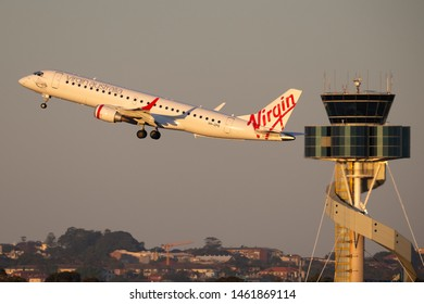 Sydney, Australia - October 9, 2013: Virgin Australia Airlines Embraer E-190 twin engine regional jet airliner landing at Sydney Airport with the air traffic control tower in the background.