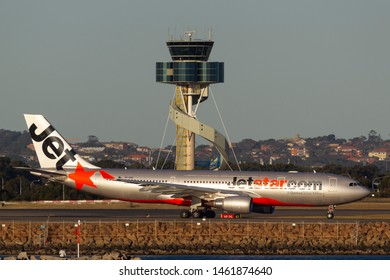 Sydney, Australia - October 9, 2013: Jetstar Airways Airbus A330 aircraft taxis past the air traffic control tower at Sydney Airport.