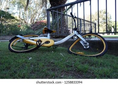 Sydney, Australia - September 30, 2018: Damaged ride share bicycle obike lay abandoned on a grass strip in Sydney.
