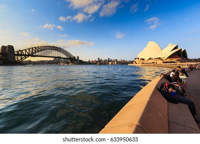 SYDNEY- AUSTRALIA- SEPTEMBER -7 -2016: People passing and take a rest by the Opera bar next to Sydney Opera house, view in Sydney, Australia,evening scene with warm light