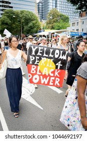 """Sydney, Australia: Two asian female protesters holding 'YELLOW PERIL 4 BLACK POWER"""" sign at Invasion Day Rally on 26 Jan 2018. Rally organised by FIRE Aboriginal Grassroots group."""
