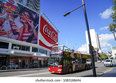 A Sydney bus tour, hop on hop off bus running in kings cross area, with coca cola billboard in background,  is the perfect way to see all the city's famous attractions in Sydney, Australia: 02/04/18