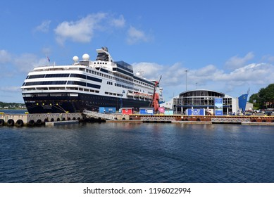 Sydney, Canada - August 8, 2018: The Holland America Massdam docked near the Joan Harris Cruise Pavilion, and the world's largest fiddle in Sydney, Cape Breton, Nova Scotia.