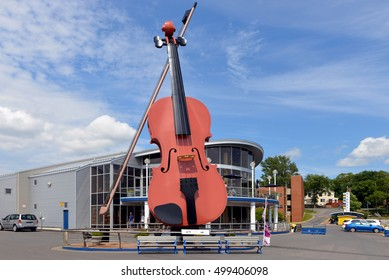 SYDNEY, CANADA - JUL 29, 2016: A monument to the Celtic heritage of Cape Breton the world'??s largest fiddle installed at the Sydney Marine Terminal in 2005 in front of the Joan Harriss pavilion.