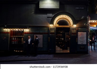 Sydney CBD, Australia - September 6 2018: Two men smoking cigarettes and chatting outside alleyway bar during the night