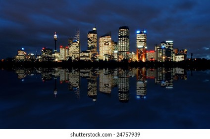 sydney cbd panorama at night, buildings reflection in water, dark cloudy night sky