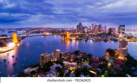 Sydney city CBD from Blues Point and North Sydney at sunset with bright illiumination of famours landmarks around Harbour in elevated aerial shot.