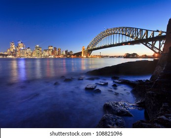 Sydney city cbd and harbour bridge view at sunset with illumination of lights at low tide Australia