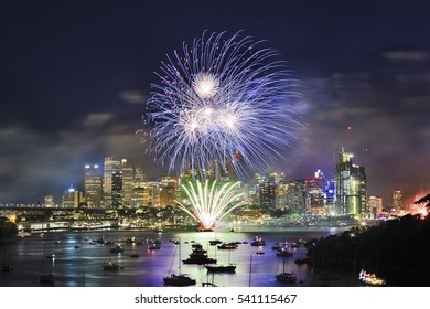 Sydney city CBD at New Year eve Fireworks over still water of Harbour. Blue light ball illuminate towers and landmarks of the city during NY light show.