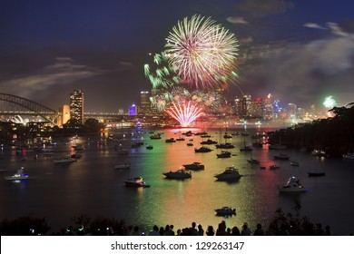 Sydney city family firework new year eve celebration illumination art pyrotechnics with reflection of bright lights in sydney harbour waters