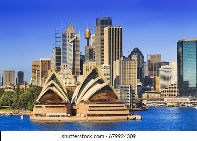 Sydney city landmarks and high-rise towers across harbour on a bright sunny day - modern architecture of office and business buildings.