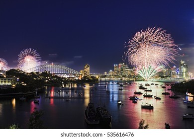 Sydney city landmarks panorama from Waverton elevated park at New Year Fireworks when bright light balls illuminate Harbour Bridge, skyscrapers and docked yachts of spectators.