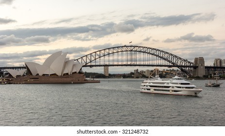 SYDNEY - DECEMBER 27, 2013: Sydney Boat Tour Harbour Cruise in Circular Quay under Sydney Harbour Bridge near Sydney Opera House under Dramatic Golden Sky at Sunset