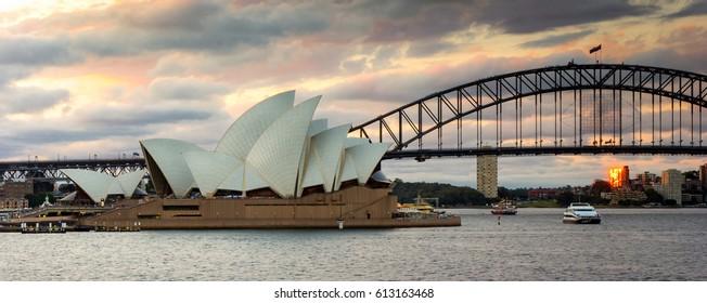 SYDNEY - DECEMBER 27, 2013: Sydney Ferry Boat Tour Harbour Cruise in Circular Quay, Illuminated Sydney Opera House and Sydney Harbour Bridge under Dramatic Golden Sky at Sunset