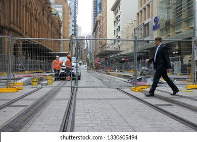 SYDNEY - FEB 21 2019:Businessman walking over Sydney CBD Light Rail.Sydney light rail sub-contractor, Acciona, seeking $1.1 billion from New South Wales Government after claiming it was misled.