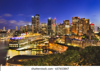Sydney harbour around Circular quay and the Rocks brightly illuminated at sunset. Popular tourism destination from overseas passenger terminal and sydney landmarks.