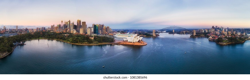 Sydney harbour around city CBD with famous landmarks and Sydney Harbour bridge at sunrise in aerial panorama.