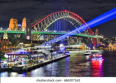Sydney harbour bridge brightly illuminated and sending blue beams of projector light during Vivid Sydney light and ideas show in Sydney CBD as seen from Circular quay towards The Rocks.