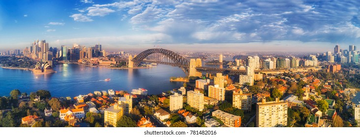 Sydney harbour with harbour bridge and city CBD landmarks from Kirribilli residential suburb and North Sydney CBD in wide aerial panorama on sunny morning.