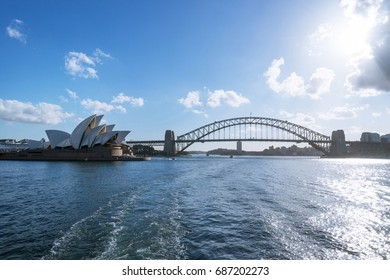 The Sydney Harbour Bridge and Opera House on sun through clouds with blue sky, clear day, background. - view from boat.