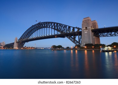Sydney Harbour bridge still arch illuminated at sunrise blue water and sky