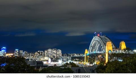 Sydney Harbour Bridge and surrounding cityscape illuminated at night in Australia