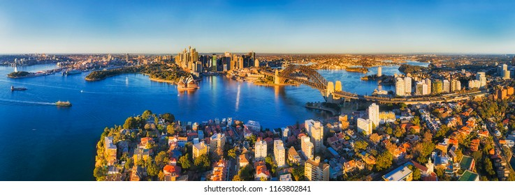 Sydney harbour shores in view of city CBD landmarks and the Harbour bridge connecting to North shore with Kirribilli residential suburb around Warringah freeway.