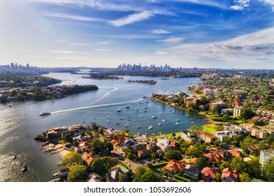 Sydney inner west suburb Drummoyne and beyond on shores of Parramatta river flowing into Sydney harbour with distant city CBD on horizon in elevated aerial view.