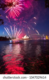 Sydney, New South Wales / Australia - February 14, 2018: Fireworks erupt over Sydney Harbour. The lights reflect off the water as Sydneysiders celebrate Valentine's Day.