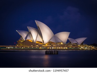 Sydney, New South Wales / Australia - April 29 2015: long exposure low key image of illuminated Sydney Opera House with flat water surface and hand rail in foreground and cloudy sky in background