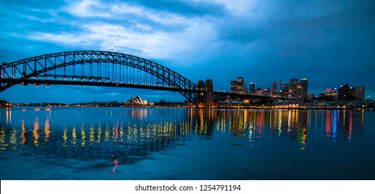 Sydney, New South Wales / Australia - October 06 2008: early morning views of illuminated Sydney Harbour with bridge and Opera House in background and projections on water surface in foreground