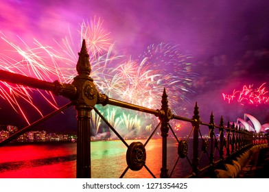 Sydney, New South Wales / Australia - 01/01/2019 New Year Fireworks illuminate the sky silhouetted by railings.