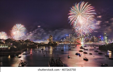Sydney New Year eve fireworks over Harbour with bridge and city CBD buildings reflecting colourful fire balls in blurred water.