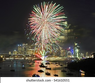 Sydney New Year Fireworks over city CBD and harbour waters with crowd of spectators and yachts. Multi-colour light balls in the sky illuminate Australian landmarks.