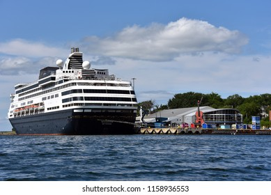 Sydney, Nova Scotia, Canada - August 8, 2018: The Holland America Massdam docked near the Joan Harriss Cruise Pavilion, and the world's largest fiddle in Sydney, Cape Breton, Nova Scotia.
