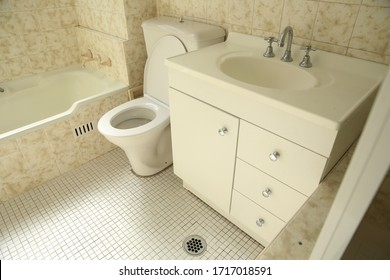 Sydney, NSW / Australia - April 28th 2020 - an ageing 1970s style bathroom with yellow and white wavy tiles, a bathtub, toilet and vanity sink