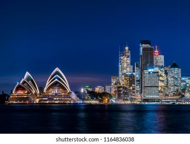 SYDNEY, NSW / AUSTRALIA - August 7, 2018: Sydney Skyline next to the Opera House at Night Just After Sunset