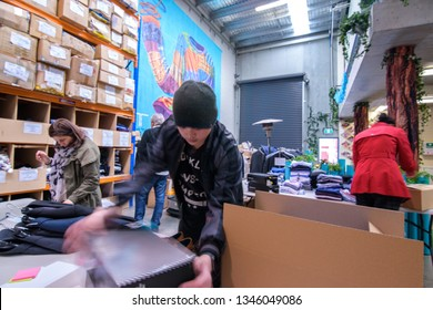 Sydney, NSW / Australia - August 8th, 2018: A group of volunteers working together in warehouse for a local nonprofit clothing charity dedicated to helping the local community and people in need