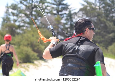 Sydney, NSW / Australia - December 23 2017: Man in a black wet suit holding on to his flying kite by the control bar. The board is under his arm and he is wearing a harness. Background: trees and sand