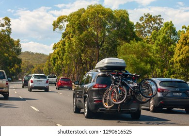 Sydney, NSW / Australia - December 30 2018: Beautiful landscapes of Australia, NSW. A car traveling on vacation with a roof rack and three bikes on the back.