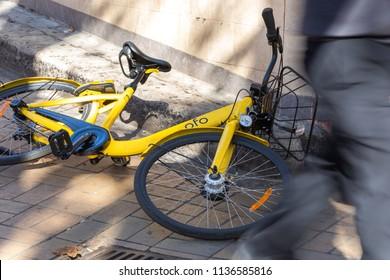 SYDNEY, NSW / AUSTRALIA - July 12, 2018: A yellow Ofo share bike is seen in abandoned on a street in Sydney.