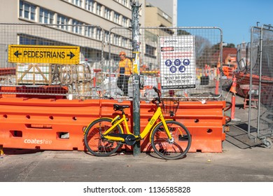 SYDNEY, NSW / AUSTRALIA - July 12, 2018: A yellow Ofo share bike is seen parked against construction works on a street in Sydney.