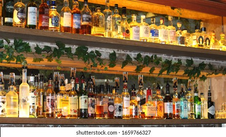 Sydney, NSW / Australia - March 1 2020: Spirits tax hike leaves Gold Coast distilleries frustrated. Pictured is a the back of a bar displaying back lit spirit alcohol bottles in a row