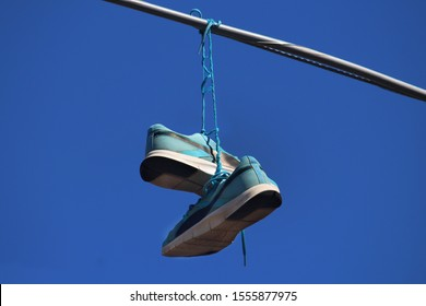 Sydney, NSW / Australia - November 4 2019: Shoes on a Wire: Untangling an Urban Myth. Pictured is pair blue runners hanging from power lines in the Inner West.