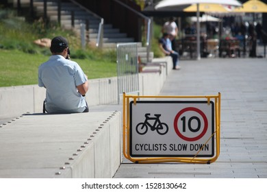 "Sydney, NSW / Australia - October 11 2019: Cyclist injuries reach record high as families fight for bike paths. Signage reading ""cyclists slow down"" indicating 10 kilometre limit. Also a boy seated."