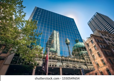 Sydney, NSW, Australia - October 21, 2019:Reflections in a glass wall of some of the most iconic landmarks in Sydney CBD including Queen Victoria Building and the City Tower Eye in Sydney, Australia.
