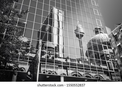 Sydney, NSW, Australia - October 21, 2019: Close up to a glass wall building in black and white with reflections in glass of Queen Victoria Building and the City Tower Eye in Sydney, Australia.